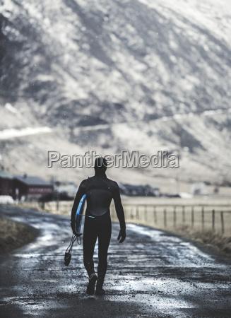 rear view of a surfer walking