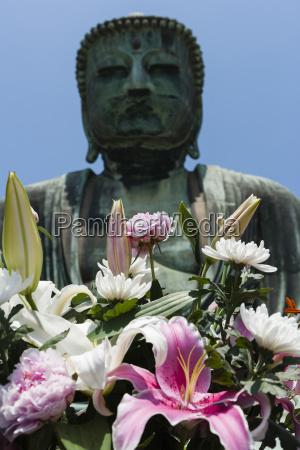 flowers in front of bronze statue