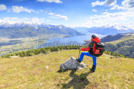 hiker on green meadows admires lake