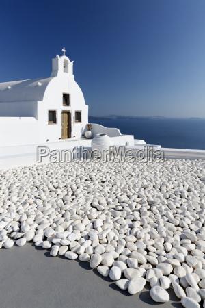 small whitewashed church against blue sea
