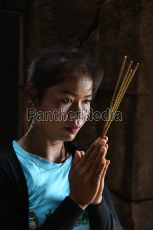 khmer woman praying in a temple