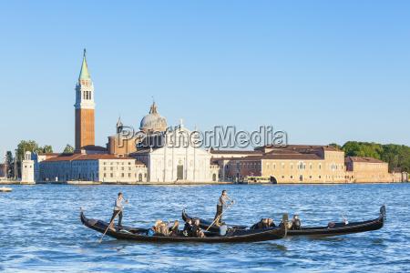 venetian gondolas with tourists opposite the