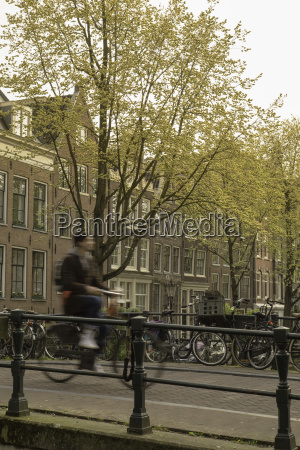 man cycling over bridge on lauriergracht