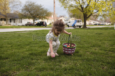 young girl standing on a lawn