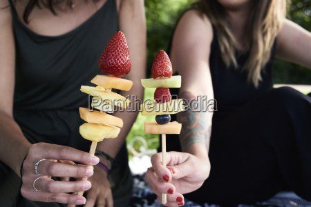 friends holding fruit skewers