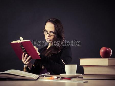 teacher sitting at her desk reading