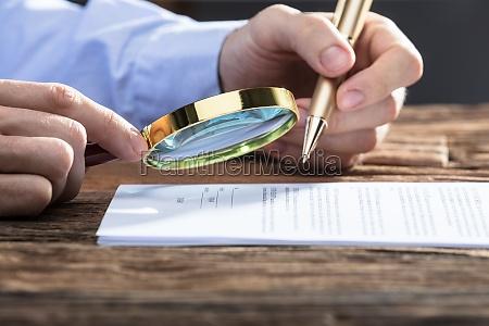 forretningsmand, kigger, på, dokument, gennem, forstørrelsesglas - 23584134