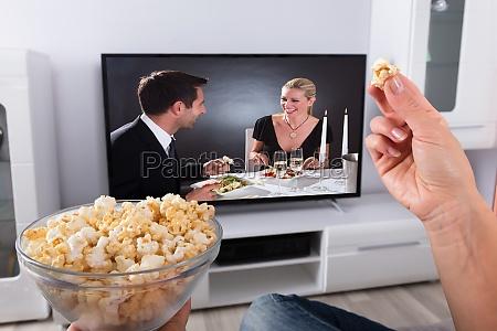 personens hand holder popcorn mens filmen