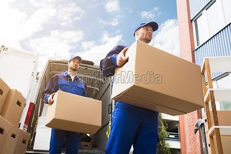 naerbillede af to leveringsmaend med papkasse