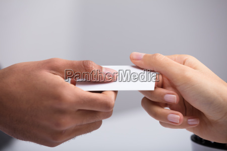 two businesspeople holding card