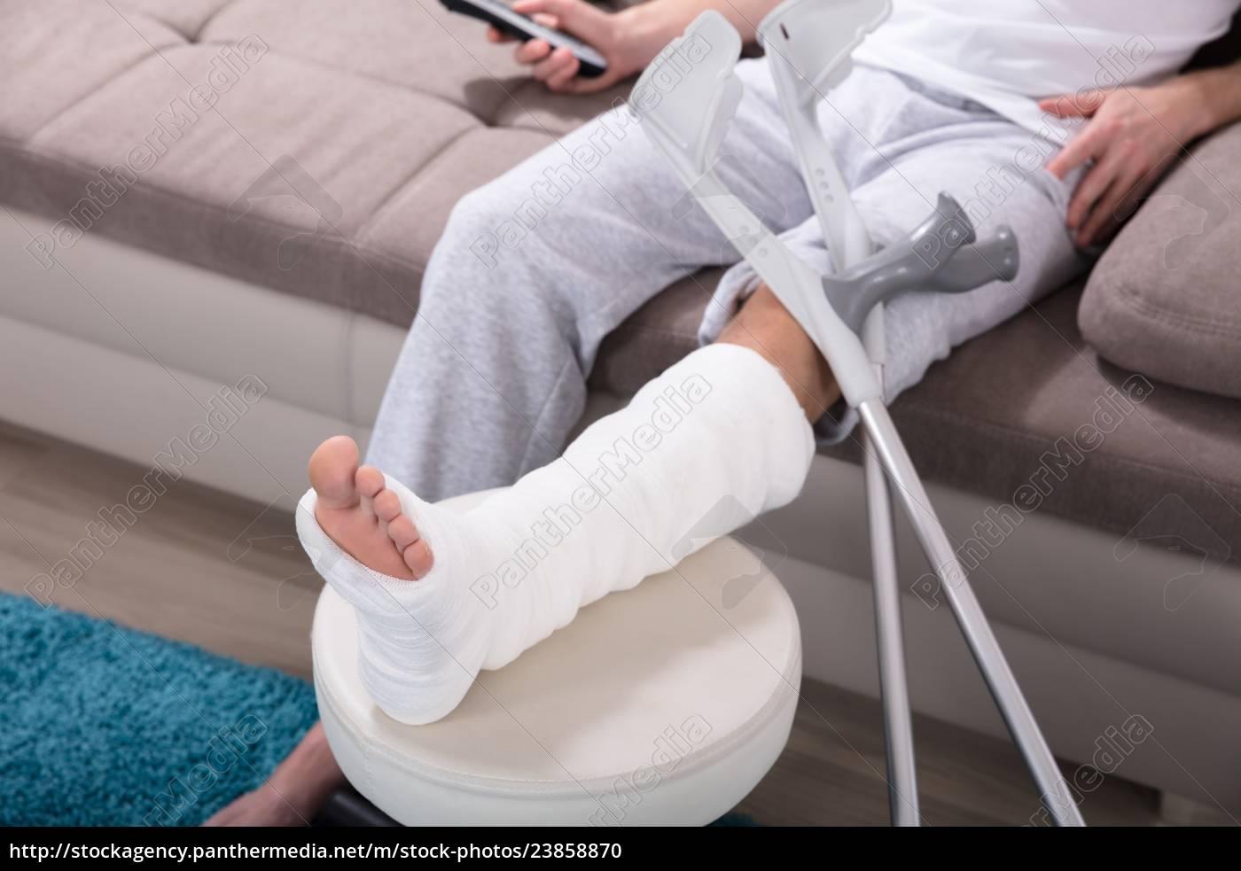Mand med brækket ben sidder på sofaen - Stockphoto - #23858870 | PantherMedia Billedbureau