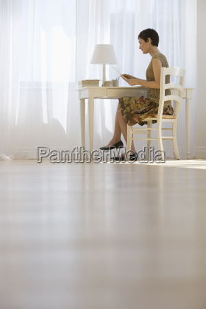 woman writing letter at desk