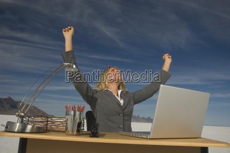 businesswoman cheering at desk salt flats