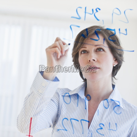 mature businesswoman writing numbers on transparent