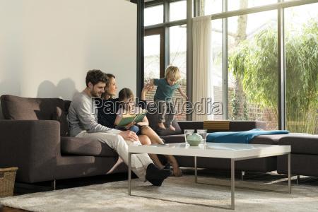 familie pa sofaen derhjemme reading bog