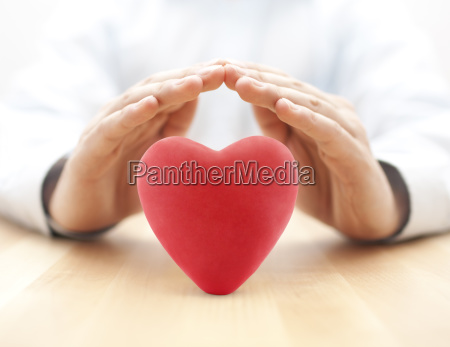 red heart covered by hands health
