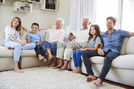 multi generation family sitting on sofa
