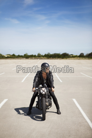 man sitting on motorcycle at field