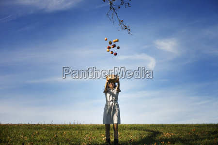 happy woman throwing apples while standing