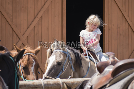 girl riding horse at barn