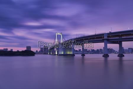 rainbow bridge over river with tokyo