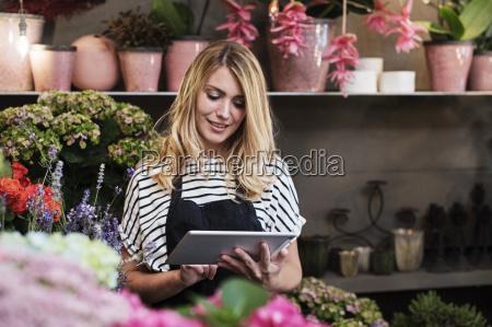 blomsterhandler bruger tabletcomputer i blomsterbutik