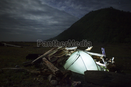 illuminated tent and logs on field