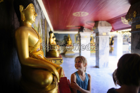 smiling girl looking at buddha statue