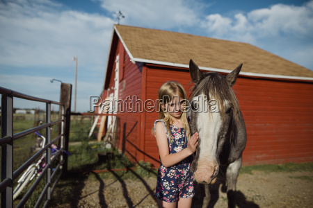 girl stroking horse while standing at