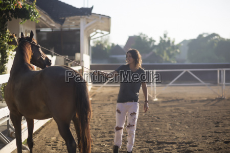 woman touching horse with animal care