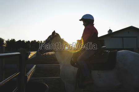 side view of girl riding horse