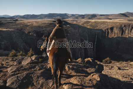 rear view of woman riding horse