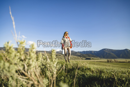 female hiker walking on field against