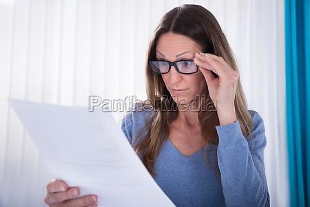 kvinde ifort briller ser pa dokument