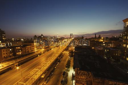 illuminated bridge and cityscape against sky