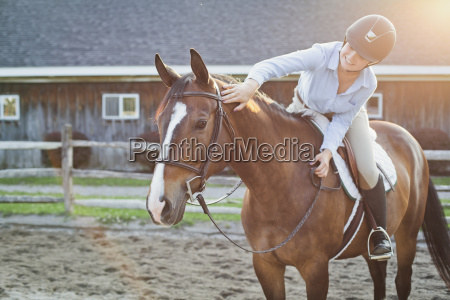 rancher petting horse while riding at