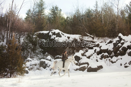 happy woman riding horse on snow