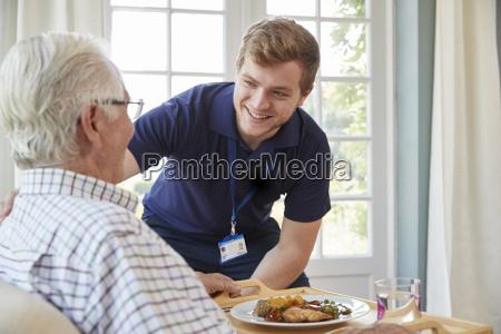 mandlige plejepersonale serverer middag til en