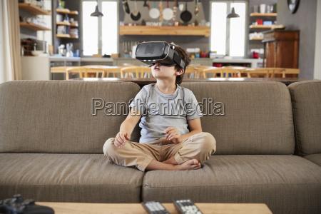 boy sitting on sofa wearing virtual