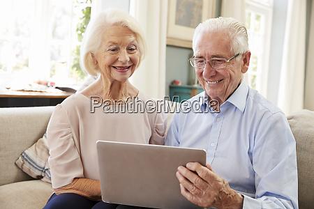 senior couple sitting on sofa using