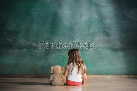 lille pige med teddybjorn sidder pa