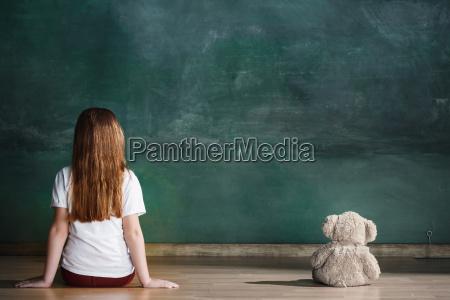 lille pige med bamse sidder pa