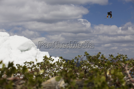 snowboarder in mid air with blue