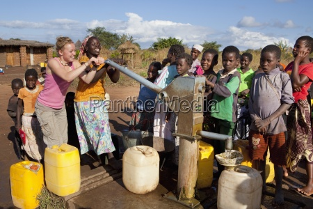 two young women pump water at