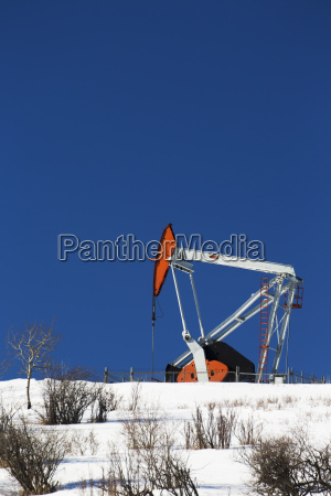 pumpjack on top of snow covered