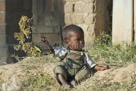 lille dreng leger med en traegren