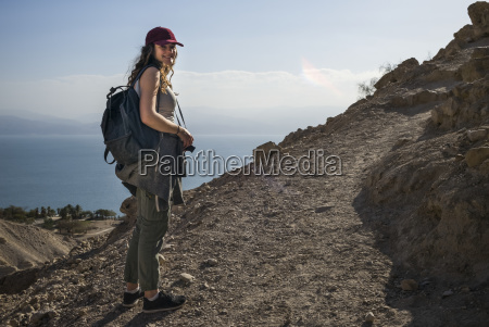 a young woman poses while hiking