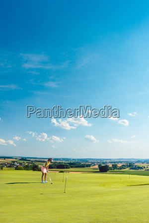 determined young woman practicing golf on