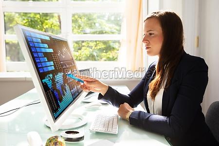 forretningskvinde analysere grafer pa computer