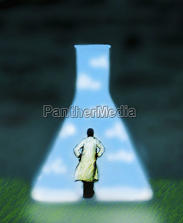 scientist looking at large conical flask